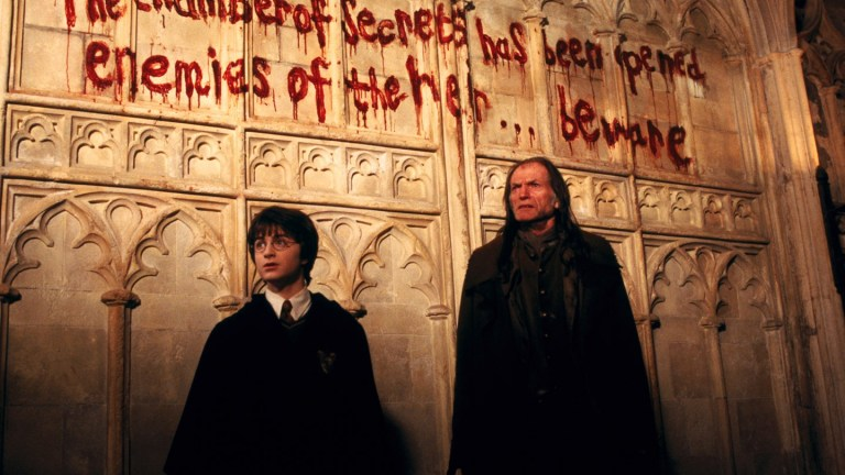 Daniel Radcliffe as Harry Potter and David Bradley as Argus Filch in The Chamber of Secrets Movie