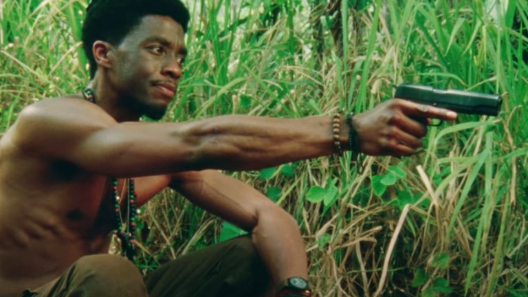Chadwick Boseman Holding Gun in Da 5 Bloods