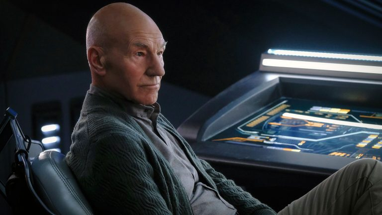 Patrick Stewart as Jean-Luc Picard, sitting in a chair on the bridge of a ship