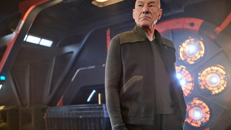 Patrick Stewart as Jean-Luc Picard stands on the bridge of a ship
