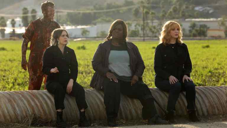 The three stars of Good Girls sit on a pipe in front of a field