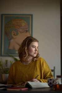 La autora Caroline Hardaker está sentada en un escritorio, bolígrafo en mano y mirando lejos de la cámara