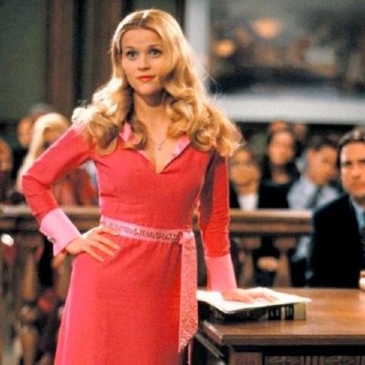 Reese Witherspoon as Elle Woods, dressed in pink, standing in a courtroom in Legally Blonde
