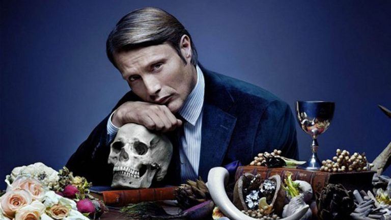 Mads Mikkelsen as Hannibal Lecter rests his head on a skull as he sits at a table adorned with flowers and wine