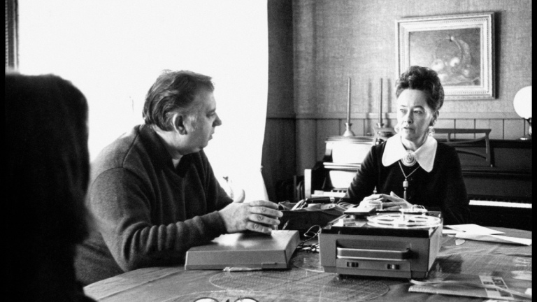 Ed and Lorraine Warren speaking at table with a tape player and record