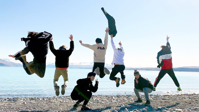 Five BTS members jump into the air while two crouch down for a picture in front of a New Zealand lake in BTS Bon Voyage Season 4