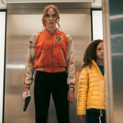 Karen Gillan as Sam stands in an elevator with a gun taped to her hand in Gunpowder Milkshake