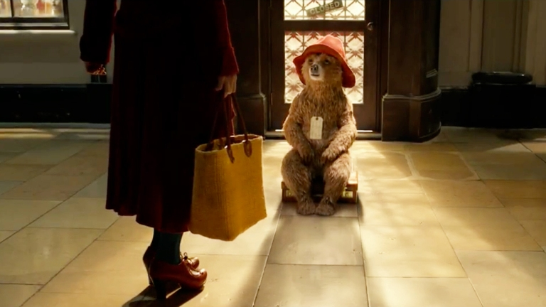 Paddington Bear sits on a suitcase; Mrs. Brown's legs appear in the foreground of the shot