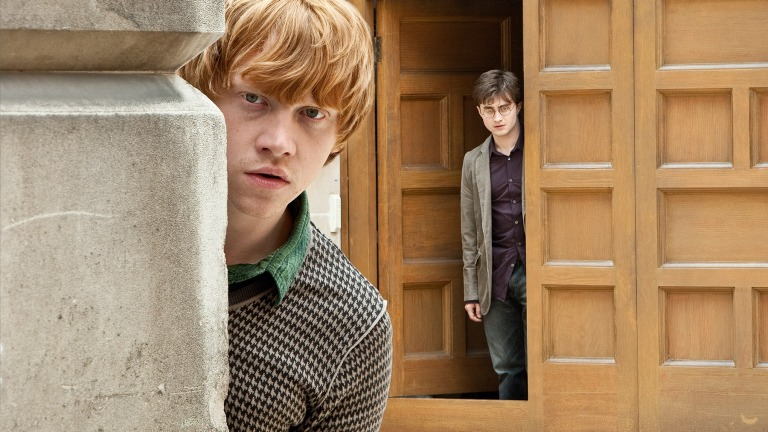 Ron Weasley peeks out from around the corner, as Harry Potter stands in a doorway in the background