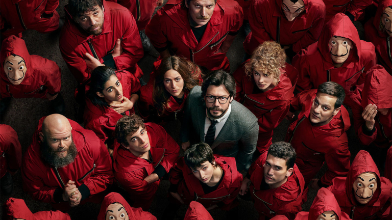 The cast of Money Heist look up in a crowd of people in red